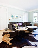Black couch, cowhide rug and dog in living area