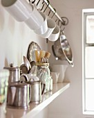 Various kitchen utensils on wall-mounted shelf