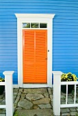 Orange louvre door of blue clapboard house with paved front path