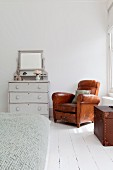 Brown leather armchair in corner of white bedroom