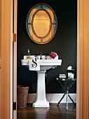 Pedestal basin against black wallpaper in elegant bathroom