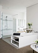 White bathtub and shower area in elegant modern bathroom