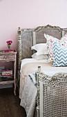 Antikes, graues Bett mit Korbgeflecht vor rosa tapezierter Wand