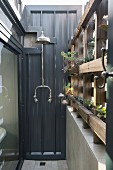 Vintage-style outdoor shower next to planted rustic wooden screen