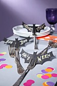 Halloween arrangement of paper bats with lettering stuck on forks on table