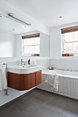Mosaic tiles and wall-length mirror in bright bathroom