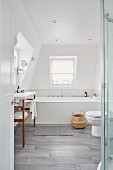 Toilet, sink and bathtub in bright attic bathroom