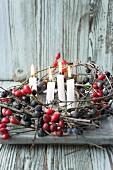 Vier Kerzen in einem Kranz aus Schlehenzweigen und Hagebutten