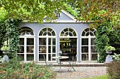 Terrace adjoining orangery with arched windows