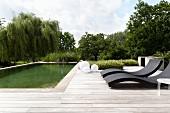 Designer sun loungers on wooden deck adjoining pool