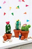 Garden gnome amongst crocheted cacti in terracotta pots