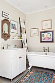 Free-standing bathtub and ladder used as towel rack in bathroom