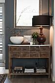 Schubladen-Kommode aus Holz vor grauer Wand mit Tischleuchte