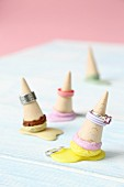 Rings placed over miniature ice-cream cones made from wood and modelling compound