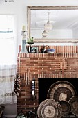 Mirror over open brick fireplace with wicker bowls