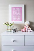 Picture with saying above the chest of drawers with flowers and dolls