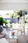Living room with window front to the summer garden with dining table