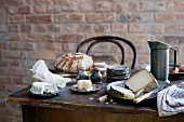 Table rustically set with pewter tableware, cheese and break in front of brick wall