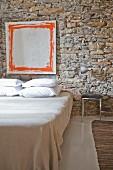 Modern artwork on rustic stone wall in minimalist bedroom