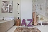 Schlafzimmer mit Leder-Teppich, lila Deko-Buchstaben und eklektischem Flair