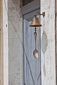 Bell with vintage spoon attached to clapper next to dove-grey front door