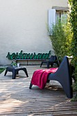 Retro neon sign and modern outdoor furniture on wooden terrace