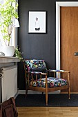 Retro armchair with colourful upholstery in front of white door frame in black wall in foyer
