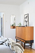 Candlesticks and picture leaning against wall op top of tall sideboard in bedroom