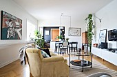 Comfortable couch, modern paintings and dining area in open-plan interior