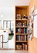 Open shelf with books and accessories and a view of an open living area