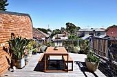 Sommerliche Dachterrasse mit Tisch und zwei Bänken unter blauem Himmel