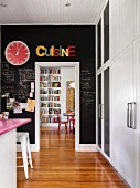 Black chalkboard paint on kitchen wall with passage into dining area