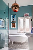 Bathroom with nostalgic freestanding bathtub, turquoise green wall paint and retro ball lamp; eclectic flair