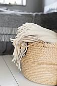 Cream woollen blanket in rattan shopping basket