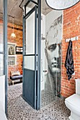 Shower with mosaic of Napoleon on wall in loft apartment with brick walls