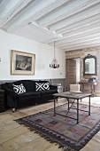 Schwarzes Sofa mit Samtbezug und Kissen und Vintage Couchtisch im Wohnzimmer mit weisser Holzbalkendecke