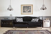 Scatter cushions on black velvet sofa, trunks used as side tables and twin chandeliers
