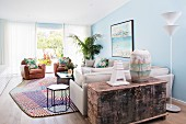 Light-flooded living room in a mix of styles with light blue walls, sofa, leather armchairs and antique wooden chest