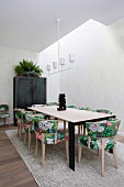 Dining area with an elongated dining table, upholstered chairs with Asian floral patterns and a white pendant lamp