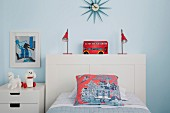 Children's room with white bed and bedside tables in front of light blue wall with red color accents through pillows, lamps and decoration