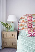 Nachtschränkchen mit Tischleuchte neben Bett mit gemustertem Kopfteil