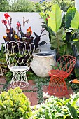 White and red wire armchairs as seating in a green garden corner
