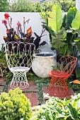 Weisser und roter Drahtsessel als Sitzmöbel in begrünter Gartenecke