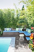 Outdoor wooden lounge area by the pool with blue upholstery and decorative pillows