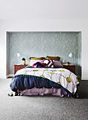 Bed with various textiles in a wallpapered alcove