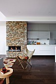 Designer chair in the open living room with fireplace and kitchen