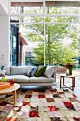 Sofa on colorful carpet in front of panoramic window to garden
