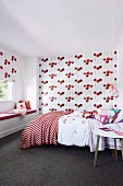 Matching patterned roller blind and wallpaper in the red and white girl's room