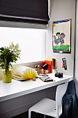 Floating desk in front of the window with black roller blind