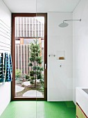 Walk-in shower with glass wall, green floor and door to the courtyard